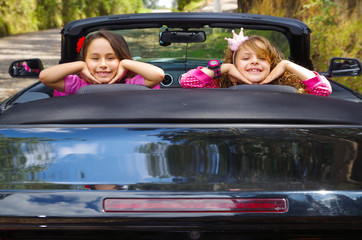 Close up of two little beatiful girls sitting in a luxury car wearing a pink clothes, enjoying the sunny day inside of the black car in a blurred background