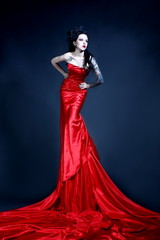 Beautiful young girl with a tattoo on her shoulder in a red dress posing in a studio on a dark background. Gothic image.