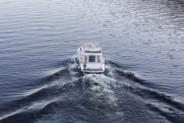Speedy luxury white motor boat on the water surface. Transport