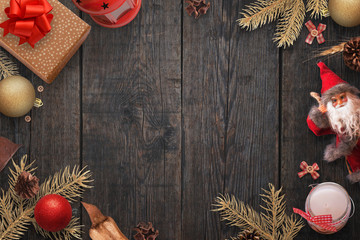 Christmas New Year background of lay gold color Christmas decorations, fir branches, gifts, balls, Santa doll, lanter, candle and blank space for a greeting text.