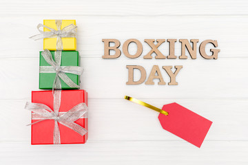 above gift boxes is tied with a ribbon with words boxing day and red