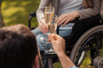Close up. Woman in a wheelchair in the park with a man. A man is sitting on blanket. They clink glasses with champagne.