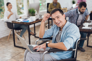 Disabled person in the wheelchair works in the office at the laptop.
