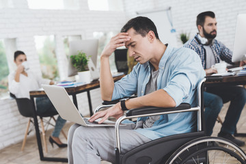Disabled person in the wheelchair works in the office. He is sitting thoughtfully.
