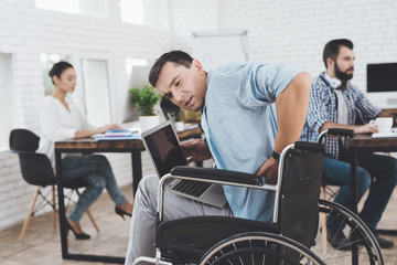 Disabled person in the wheelchair works in the office. He feel desease.