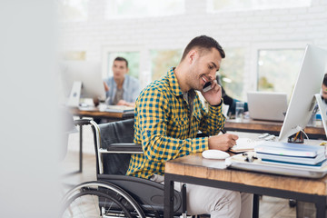 A man in a wheelchair writes with a pen in a notebook and talks on the phone. He is working in a bright office.