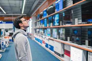 Smart modern male customer choosing large TV-sets at electronics store. He looks wondered. New screen generations. Papier Peint