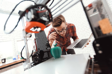 A man with a laptop in his hands controls the process of printing a 3d printer. 3d printer has printed model of an apple