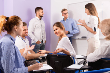 Group of students with teacher in break between lessons indoors