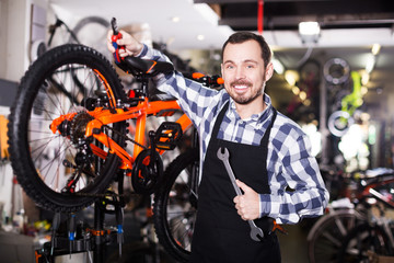Mechanic in bicycles store workshop