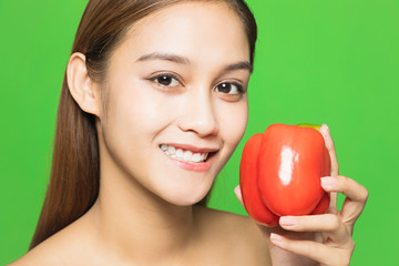 Young woman holding a red paprika.