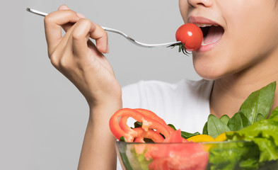 Young woman biting a salad.
