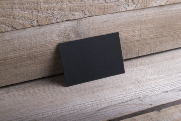 Black business cards isolated on old wood background