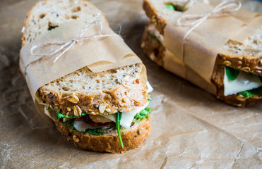 Sandwich with cereal bread, chicken, pesto and cheese on the rustic wooden background. Selective focus. Shallow depth of field.