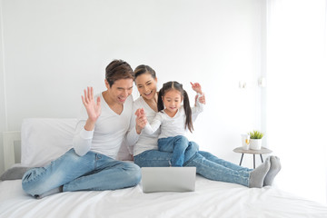 Portrait of Asian family looking at a tablet computer while lying on the bed, little asian girl using laptop with her parents. Weekend holiday leisure time education concept