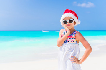 Adorable little girl in Santa hat during Christmas beach holiday