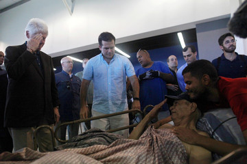 Former U.S. President Clinton salutes a man while visiting with Puerto Rico Governor Rosello a school turned shelter for people who have lost their homes during Hurricane Maria in September, in Canovanas