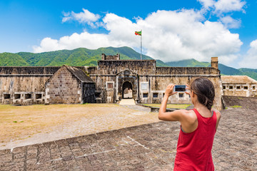 Wall Mural - St Kitts tourist woman taking picture on cruise ship travel vacation. Girl visiting St. Kitts Brimstone Hill Fortress National Park on St Kitts and Nevis. Caribbean destination cannon lookout.