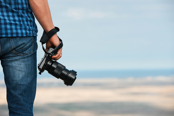Photographer holding a photo digital camera in his hands