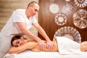 Masseur doing massage on the back of a young attractive girl in Spa salon. Girl lying with his eyes closed