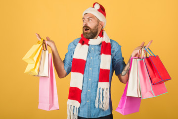 Christmas man shopper hold shopping bags on yellow background