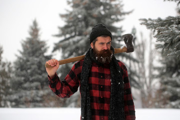 Christmas hipster lumberjack with ax in wood..