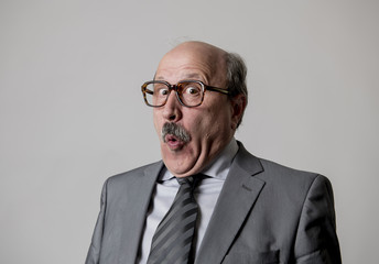 portrait of 60s bald senior happy business man gesturing funny and comic in laughter and fun face expression looking happy