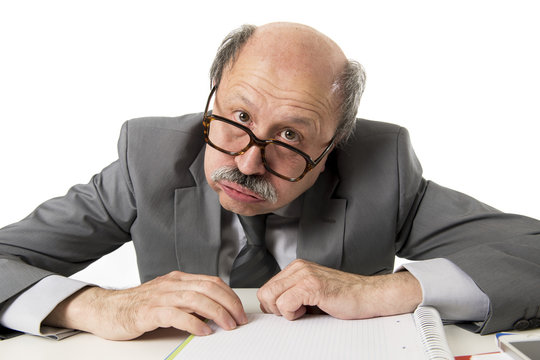 60s bald senior office employee man furious and angry gesturing upset and mad sitting on desk with paperwork in business