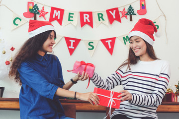 Two asia women holding gift box with happiness in Christmas party, friends Christmas party, holiday celebration, LGBT couple