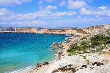 Rocky coastline with hotels to the rear, Paradise Bay, Malta.