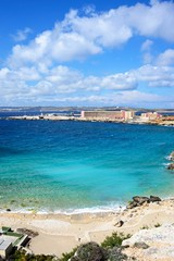 Rocky coastline with hotels and ferry terminal to the rear, Paradise Bay, Malta.
