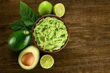 Guacamole and ingredients on dark wooden background.