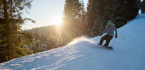 Horizontal shot of a female snowboarder riding downhill on snowy slope in the evening copyspace scenery nature mountains powder freeride snowboarding copyspace
