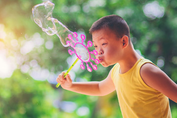 asian boy blowing soap bubbles on nature background. Outdoors at the daytime with bright sunlight.