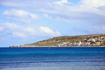 Windsurfer in the bay with town buildings and coastline to the rear, Mellieha, Malta.