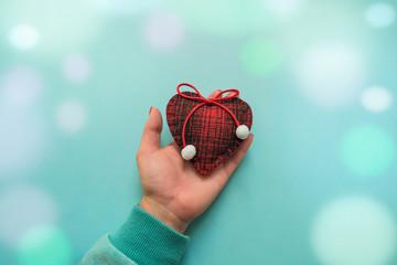 Woolen heart in his hand. Valentine Concept, bokeh.