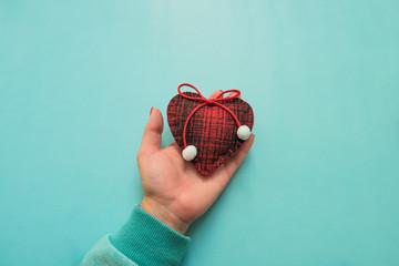 Woolen heart in his hand. Valentine Concept
