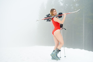 Sporty girl skier wearing swimsuit, holding skis on the shoulder, standing on the snowy slope at ski resort in the mountains. Foggy forest on the background. Ski season and winter sports concept