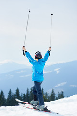 Back view of female skier wearing blue ski suit and black helmet, holding poles above a head, enjoying skiing at ski resort in the Carpathian mountains. Ski season and winter sports concept