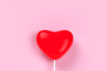 red heart lolipop on pink background, love concept, minimal style concept.