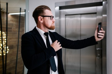 Business Concept - Portrait Handsome Business man take a selfie of himself with smartphone. background of the Elevator in the office building.