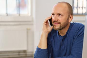 mann sitzt im büro und telefoniert