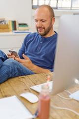 mann sitzt entspannt am schreibtisch und liest eine sms auf seinem handy