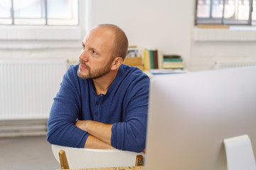 mann sitzt am computer und schaut mit ernstem blick zur seite