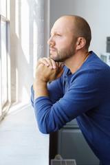 mann steht im büro und schaut grübelnd aus dem fenster