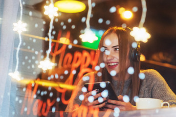 Young beautiful woman sitting in cafe, drinking coffee. Model listening to music. Christmas, Happy new year, Valentines day, winter holidays concept
