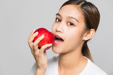 Young woman biting an apple.