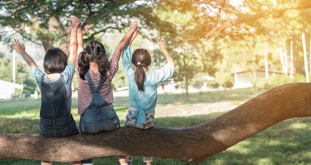 Children friendship concept with happy girl kids in the park having fun sitting under the tree shade playing together enjoying good memory and moment of student friends in old school time day