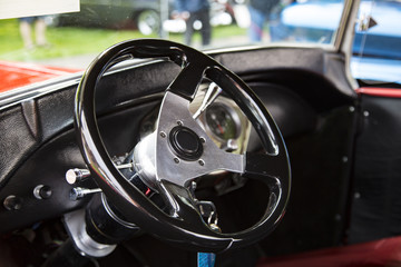 Isolated Interior View of Restored Tricked Out Vintage 50s Automobile Dashboard and Steering Wheel,  Fabric Seats, with Out of Focus People and Cars in Background