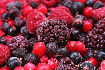 Frozen mixed berries as background. Blueberries,raspberries black berries and currant mulberry texture pattern. Photo.